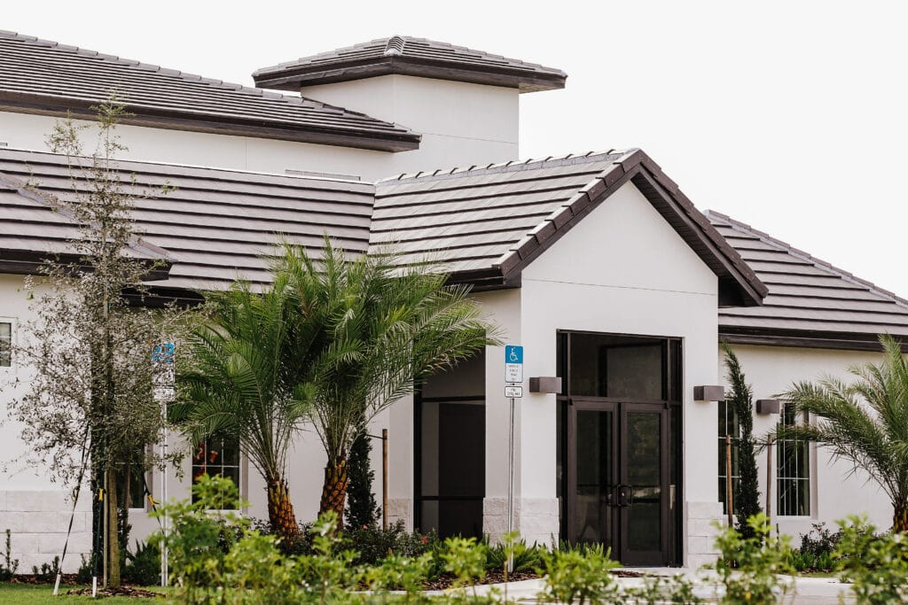 entrance to modern white building with brown tile roof and palm trees