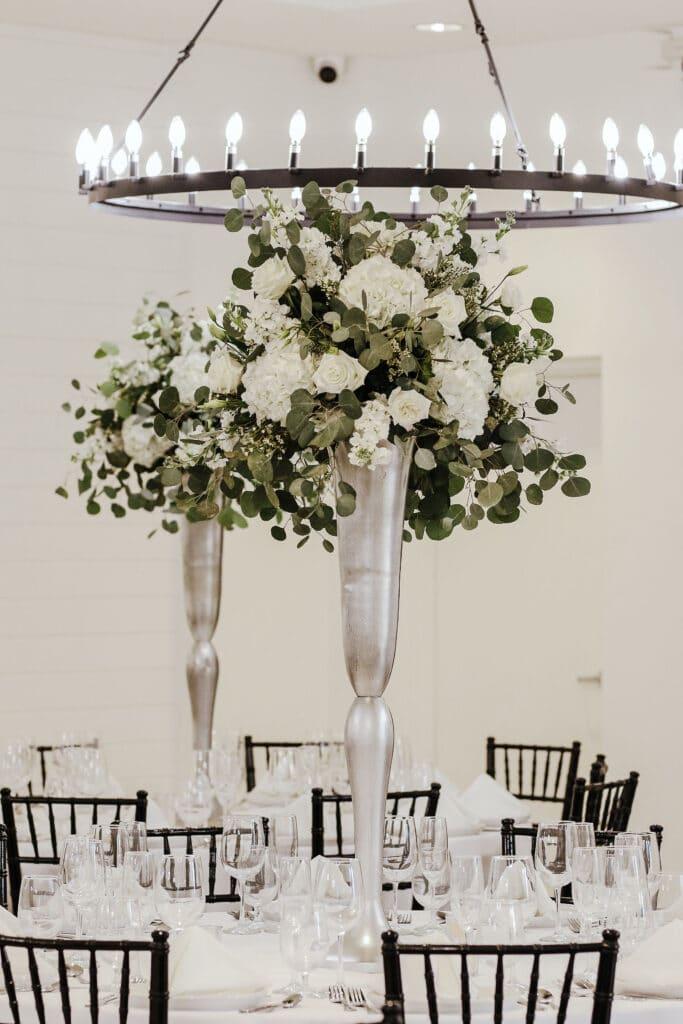 round white table with tall white floral arrangements under modern round chandelier