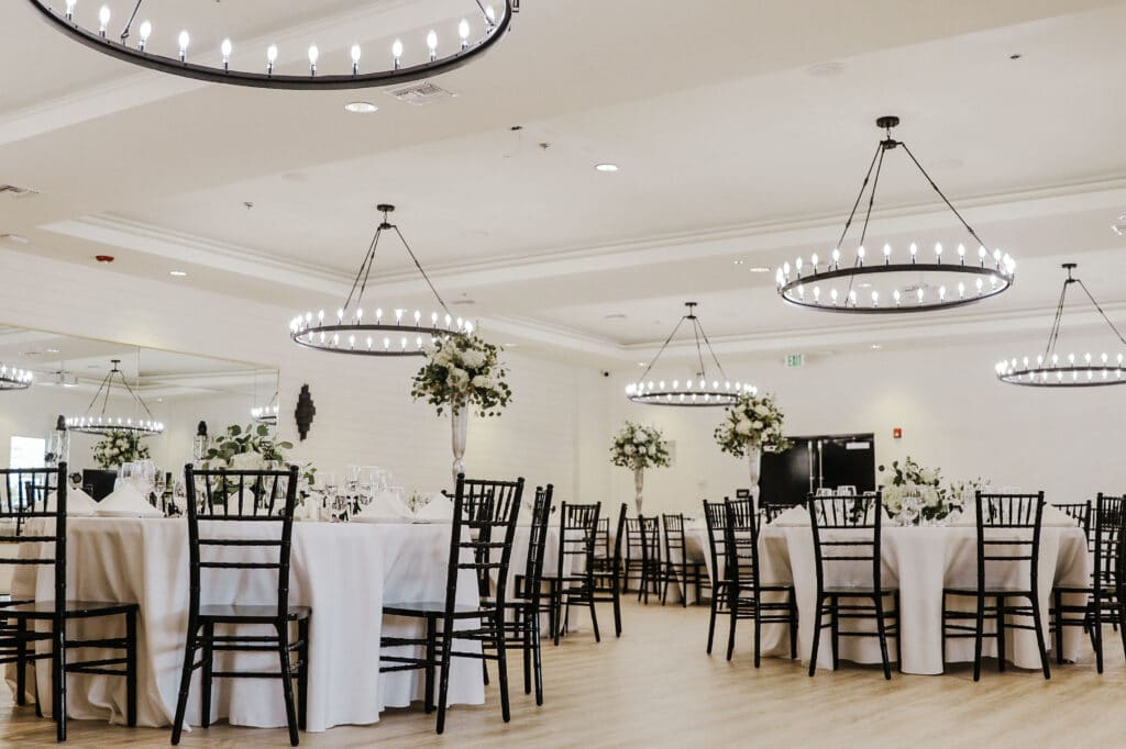 wedding reception set up with round white tables and dark chairs in a white room with modern round chandeliers