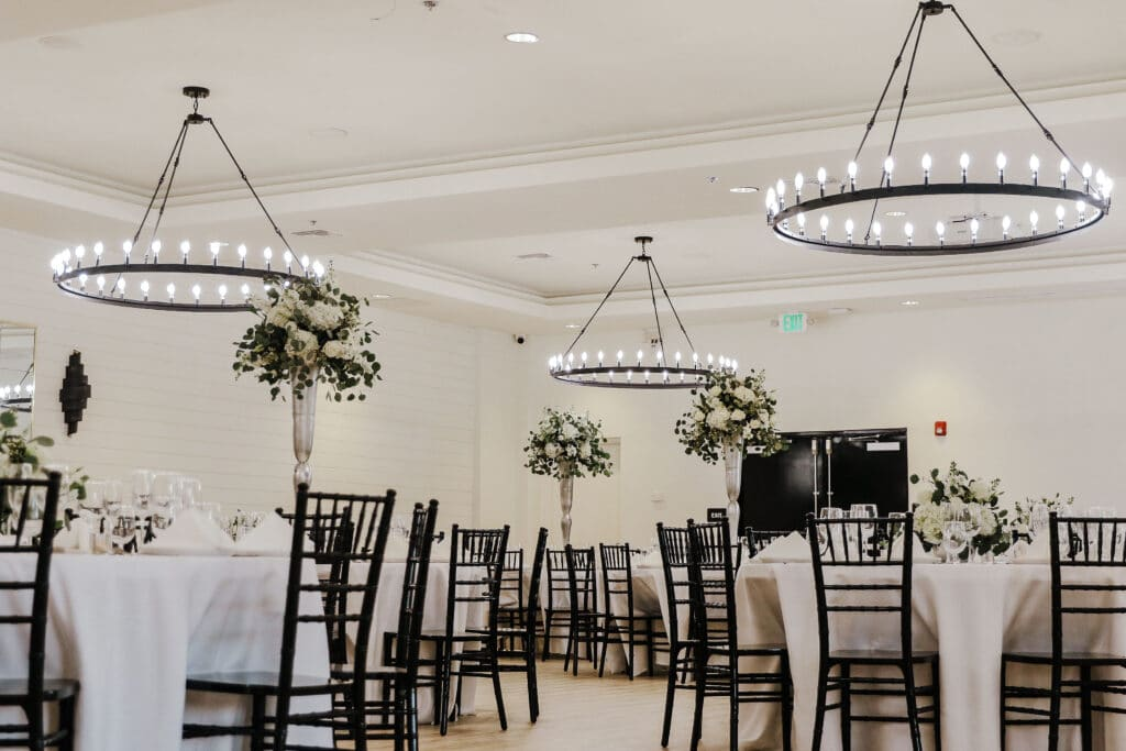 white room with round tables with large white floral arrangements and modern round chandeliers