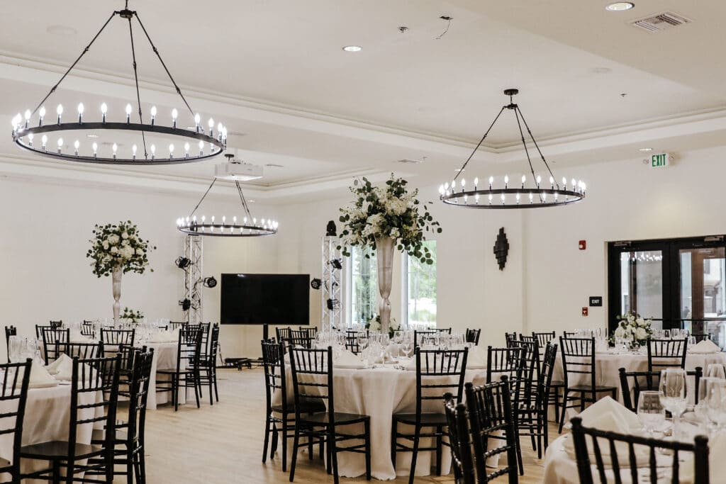 event hall with white walls, round tables, and large modern chandeliers