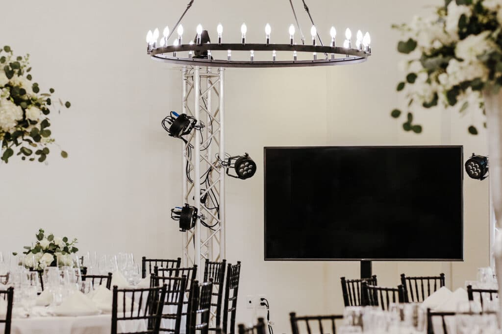 white event space with round chandelier, large tv monitor, and event lighting
