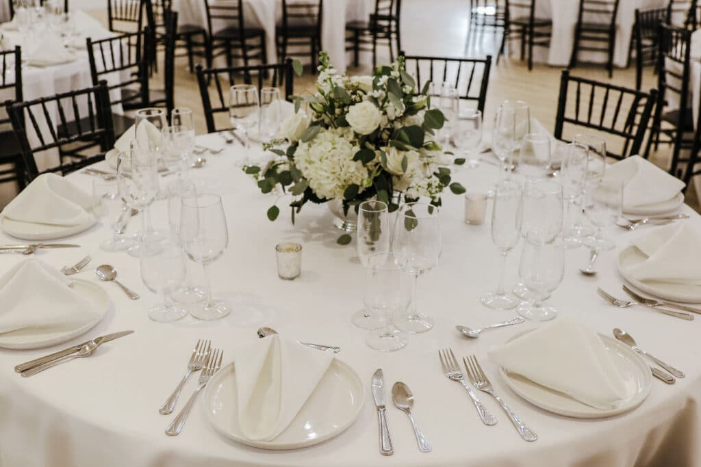 round table with white table cloth, white table settings, and small white floral arrangement