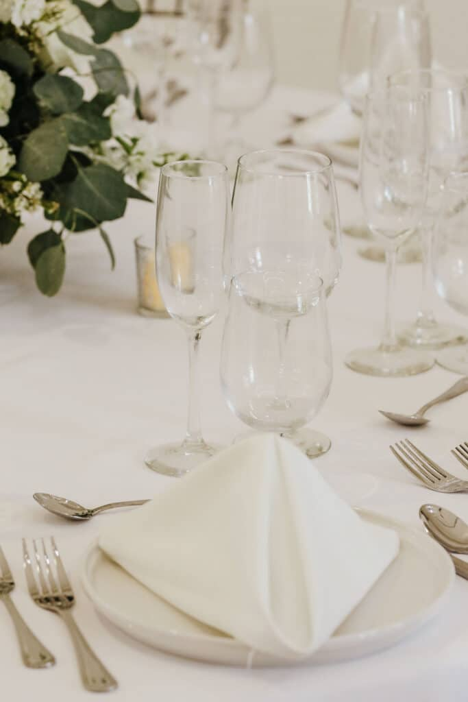 white table setting with folded cloth napkin and wine glasses on white table cloth