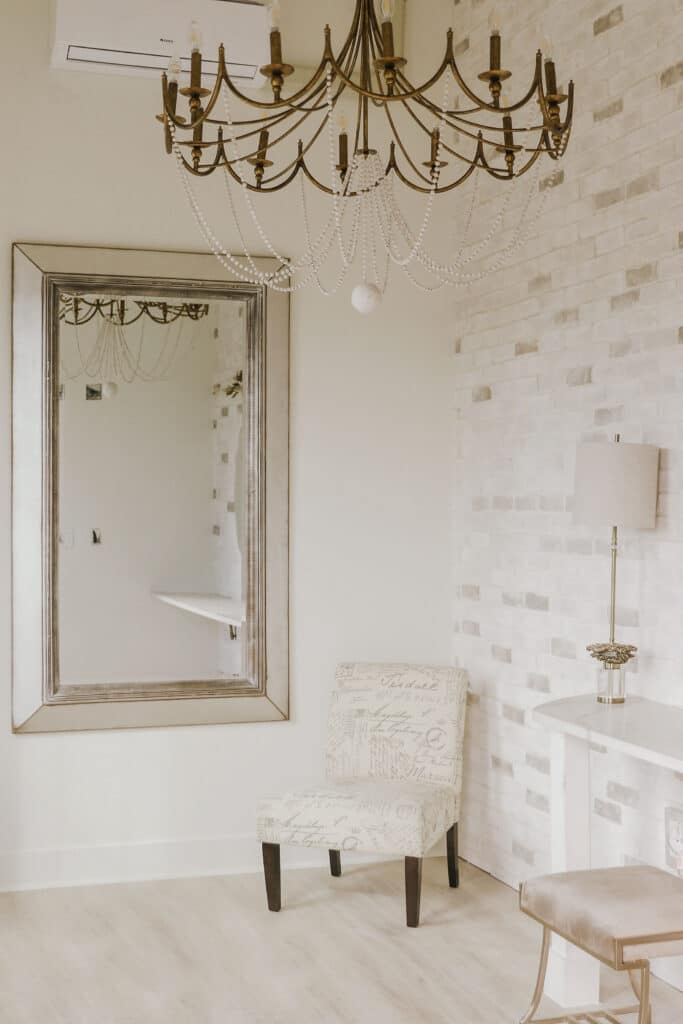 room with white walls, light wood floors, gold chandelier, and large mirror on wall with silver frame