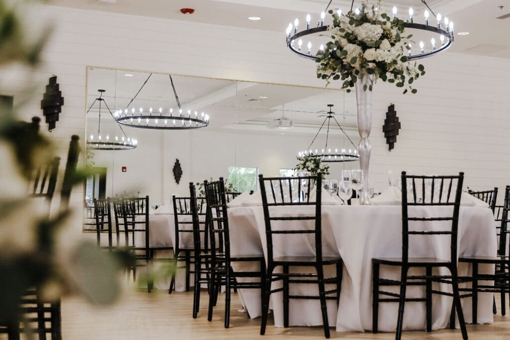 wedding reception set up with white tablecloths, dark chairs, tall white floral arrangements and modern chandeliers