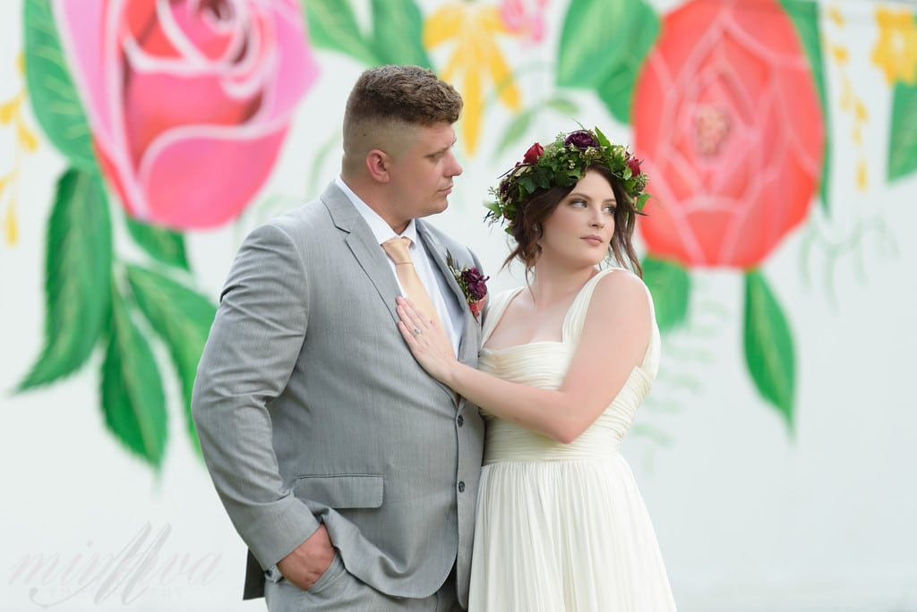 bride and groom standing in front of a mural painting of flowers while bride has her hand on grooms chest