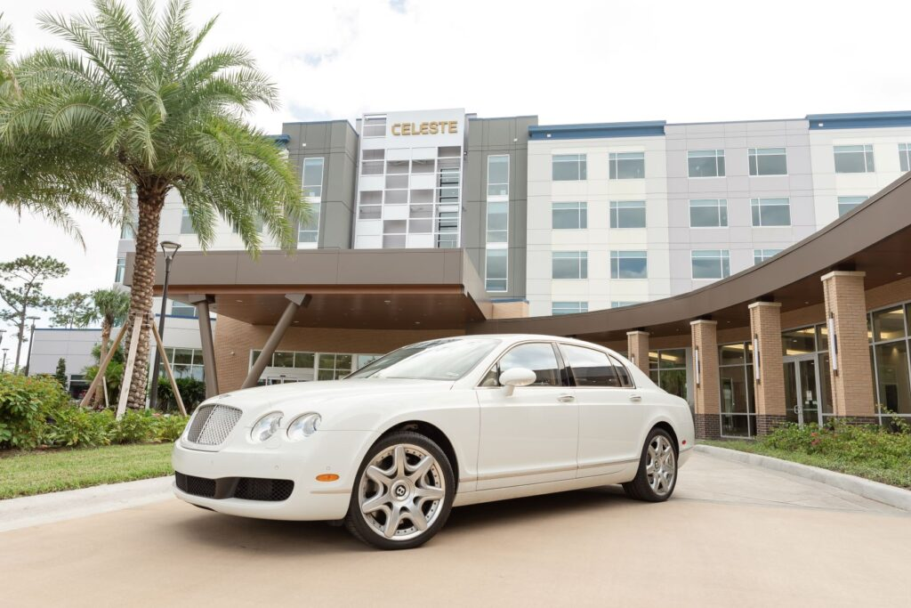 white bentley in front of the celeste hotel with palm tree