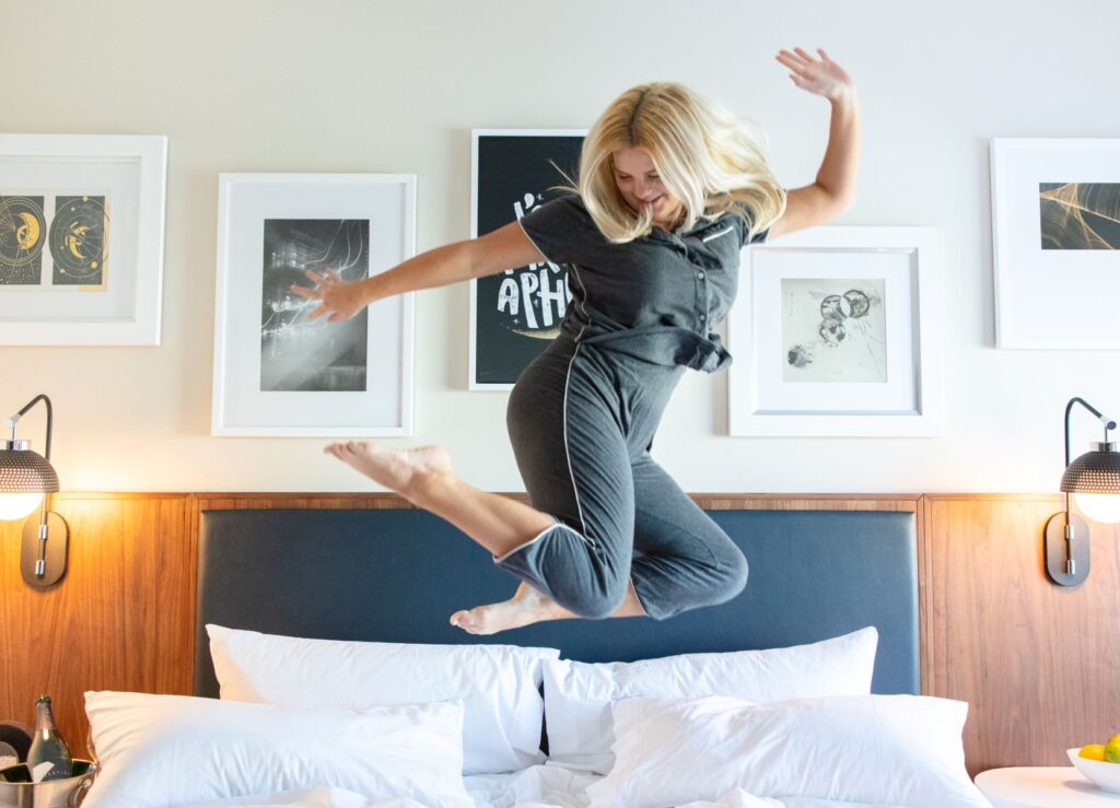 woman in gray pajamas jumping on hotel bed with framed artwork on wall