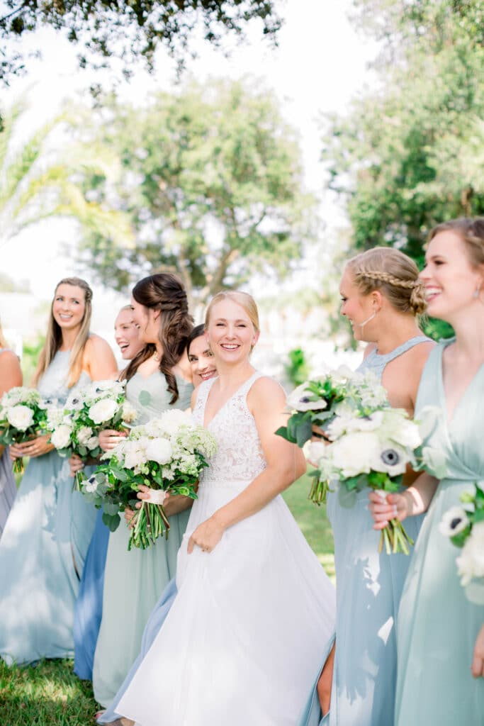 bride smiling while standing in the middle of her laughing bridesmaids wearing light blue dresses outside at The Grand Ol' Barn