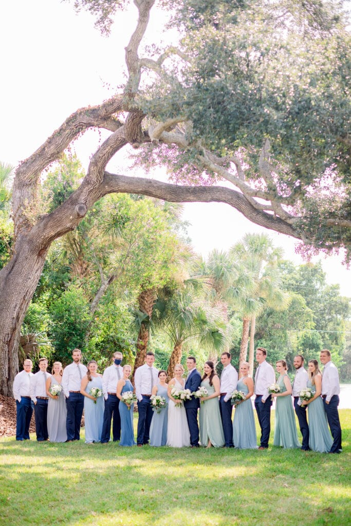 bridal party standing in line outside of The Grand Ol' Barn underneath an old tree