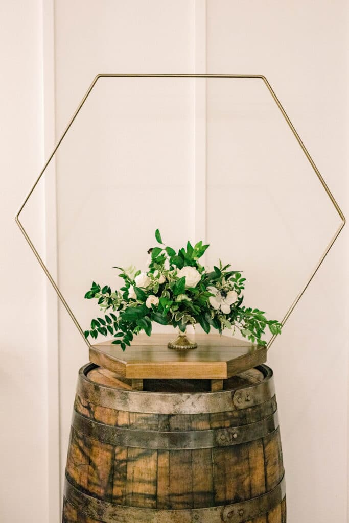 green and white flower setup as wedding decoration on old wooden barrel at The Grand Ol' Barn