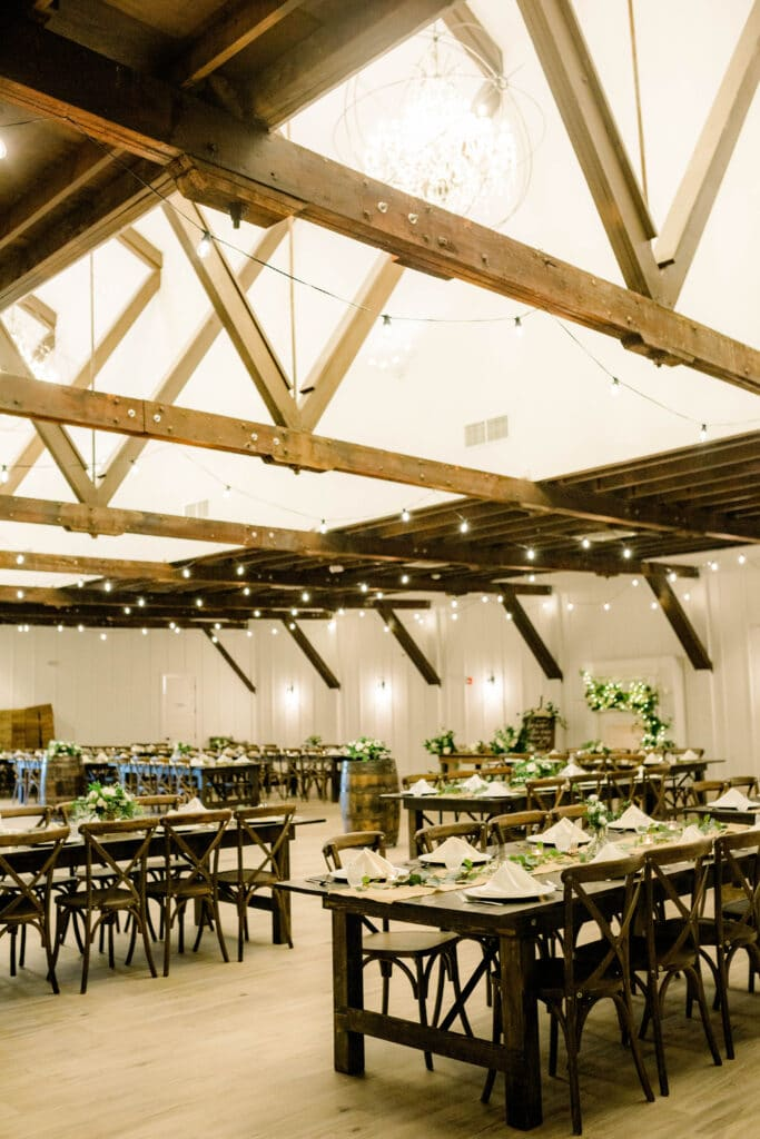 wedding reception setup inside of The Grand Ol' Barn with beautiful market lighting, long wooden tables, wooden barrels, and green and white flowers