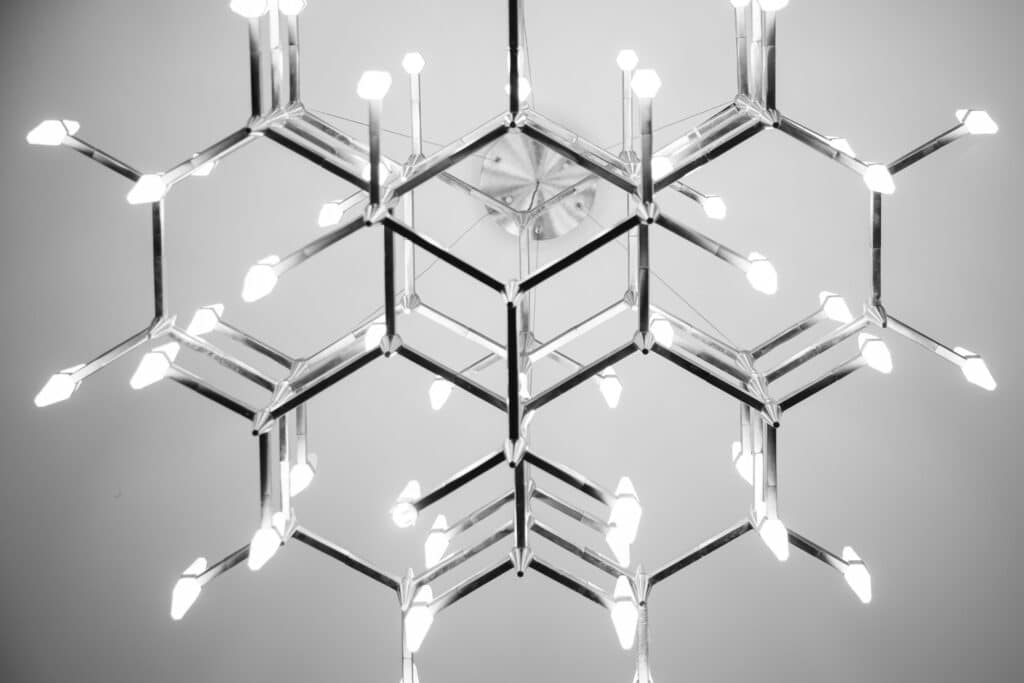 black and white image looking up at geometric chandelier