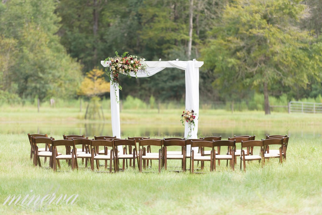 white archway setup for wedding ceremony outside with dark chairs in a semicircle in front of arch