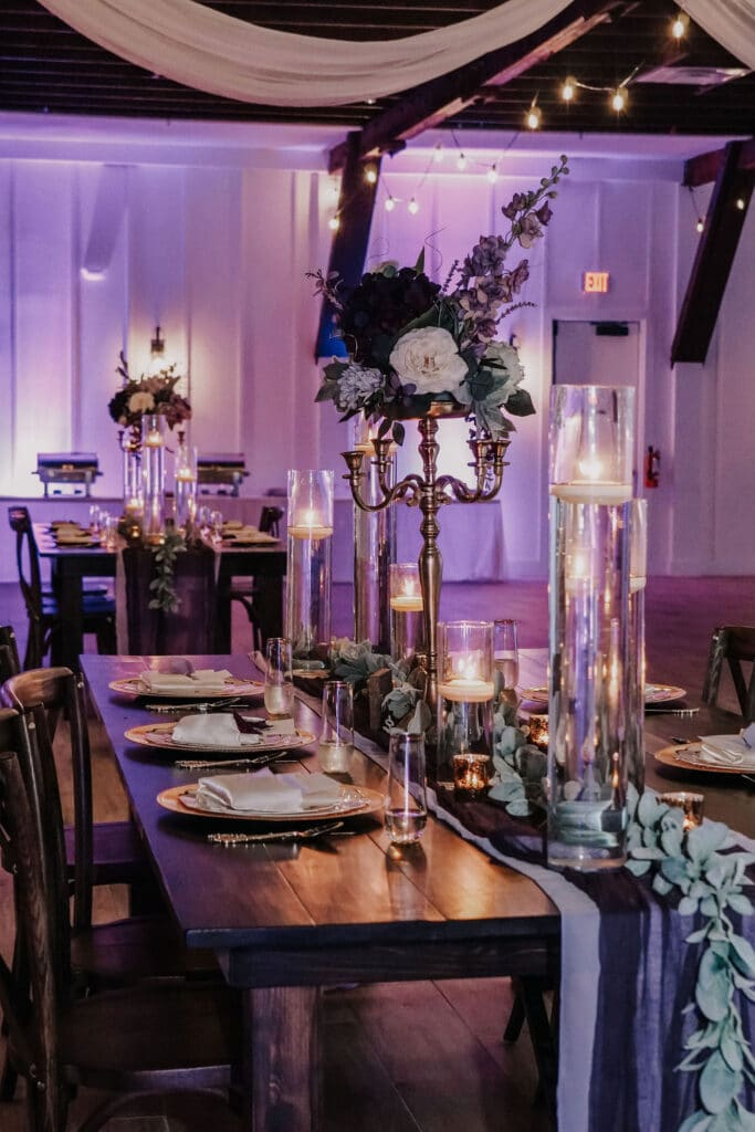 long wooden table setup for wedding reception at The Grand Ol' Barn, with tall candlesticks and flower centerpieces and floating candles