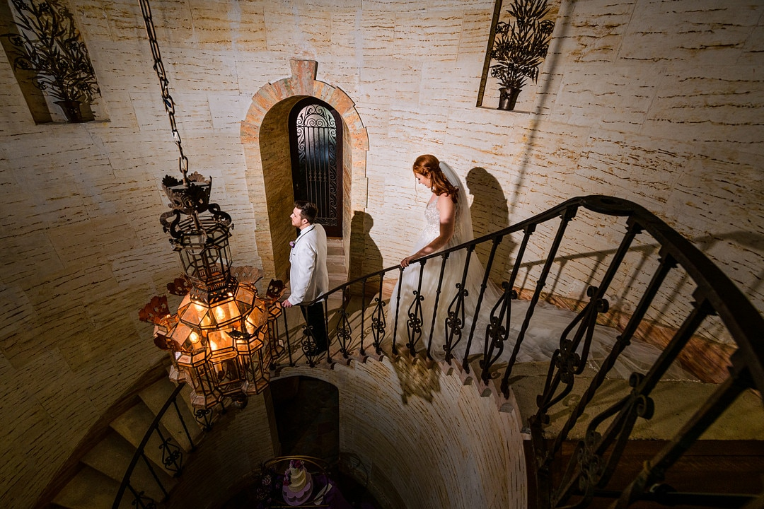 picture from above of bride walking down historic staircase at wedding venue to groom facing the opposite direction