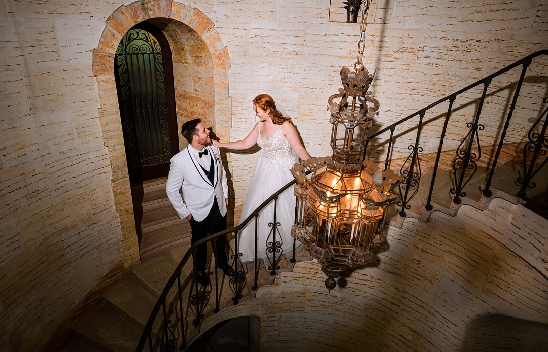 bride and groom first look on historic staircase at their florida fairy tale castle wedding