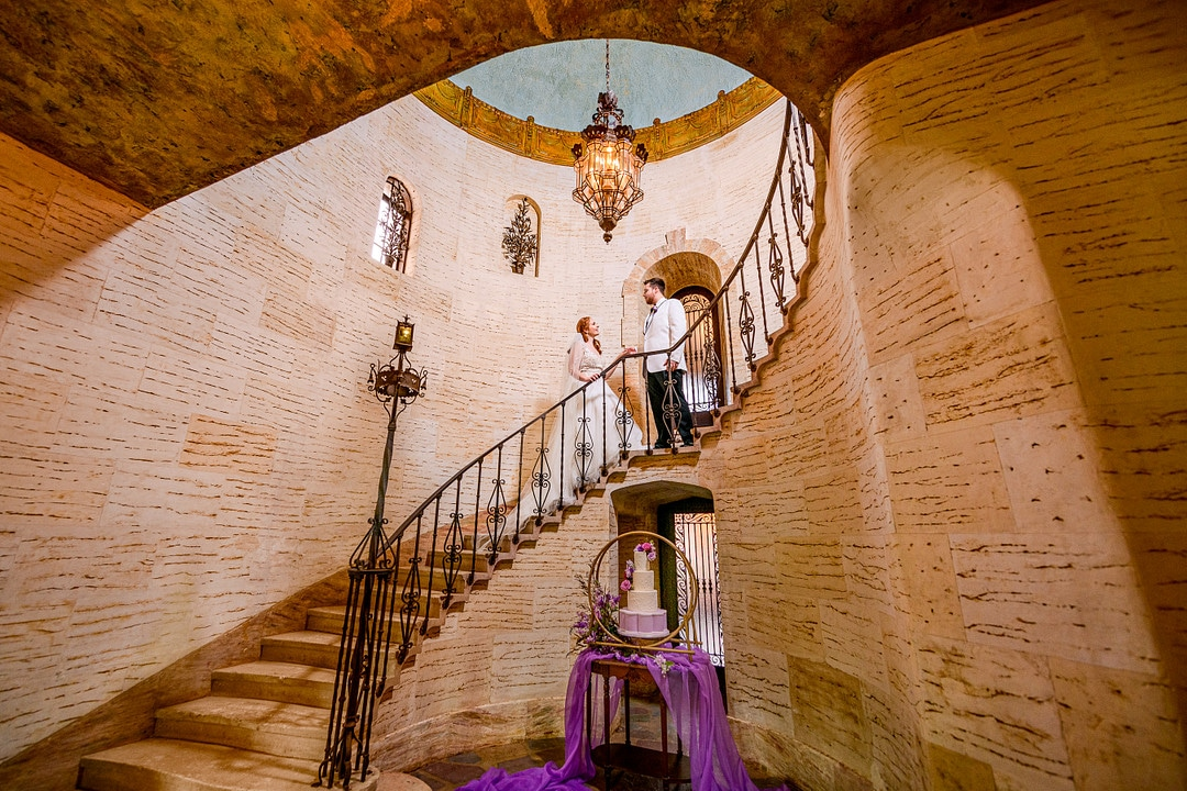 wide shot of bride and groom near the top of historic staircase with wedding cake and decorated table on the floor at the bottom of the staircase