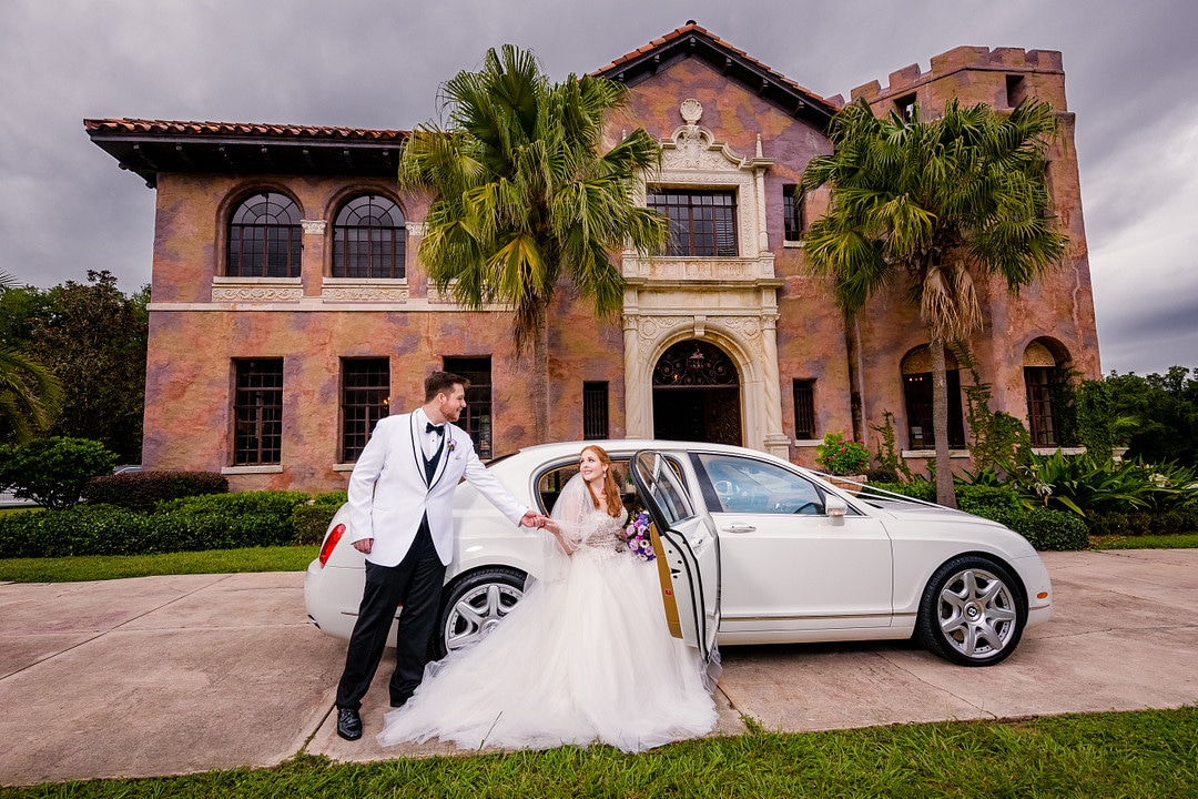 bride sitting in classic white wedding car with groom next to her outside of the door in the driveaway in front of wedding venue