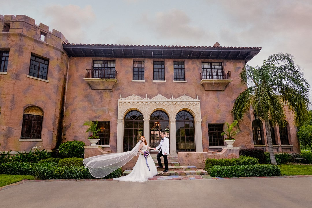 bride with floating white veil standing next to groom outside of their florida wedding venue
