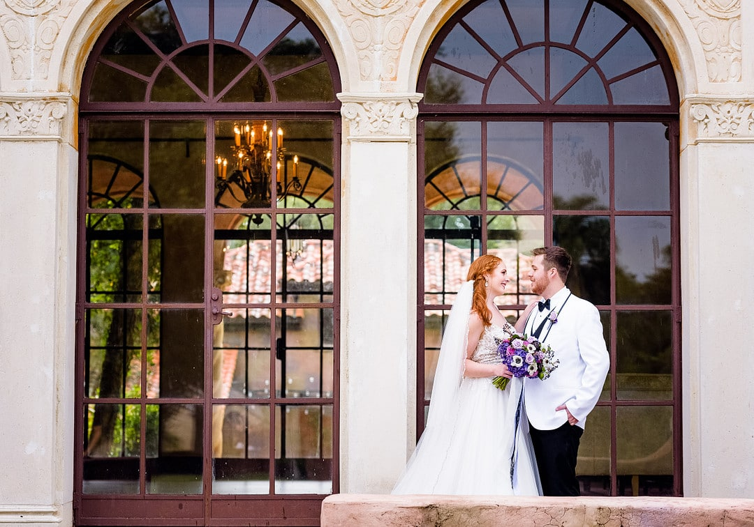 bride holding bridal bouquet and groom looking at each other for wedding portraits outside of floor to ceiling windows