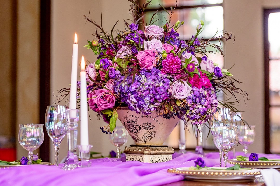 vivid purple and pink floral centerpiece on table with glassware and candles all on top of vibrant purple fabric for wedding tablescape