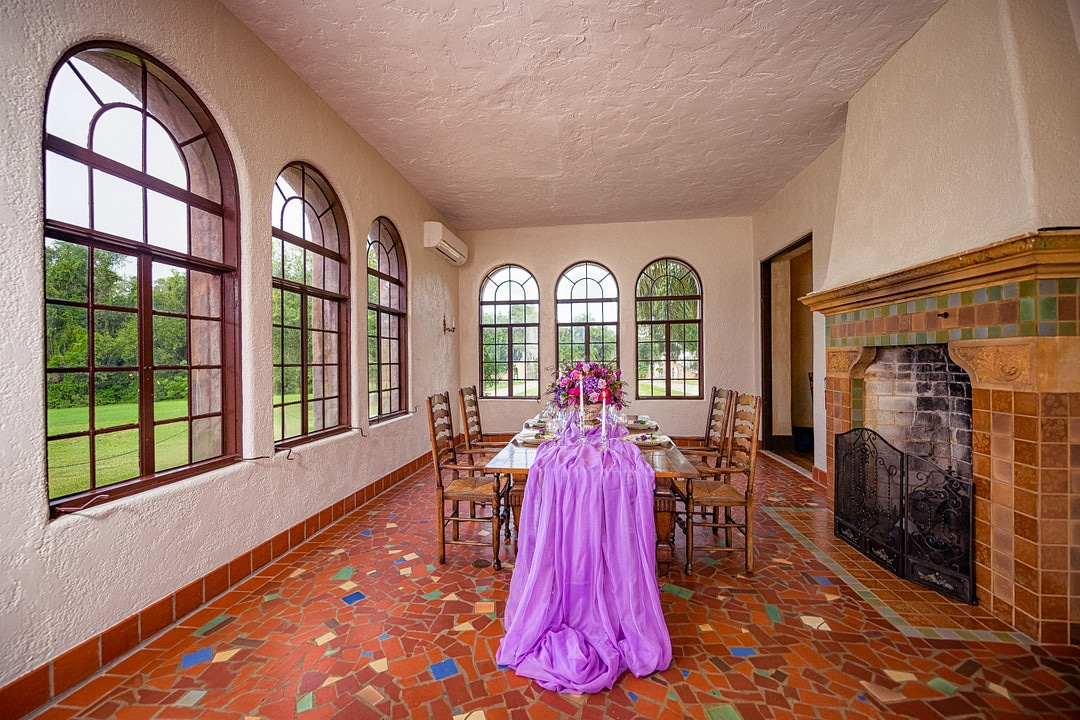 pulled back shot of one table set up for wedding tablescape with bright purple draping fabric down the middle and decor set with fireplace to the right hand side of image and windows on the left of the room