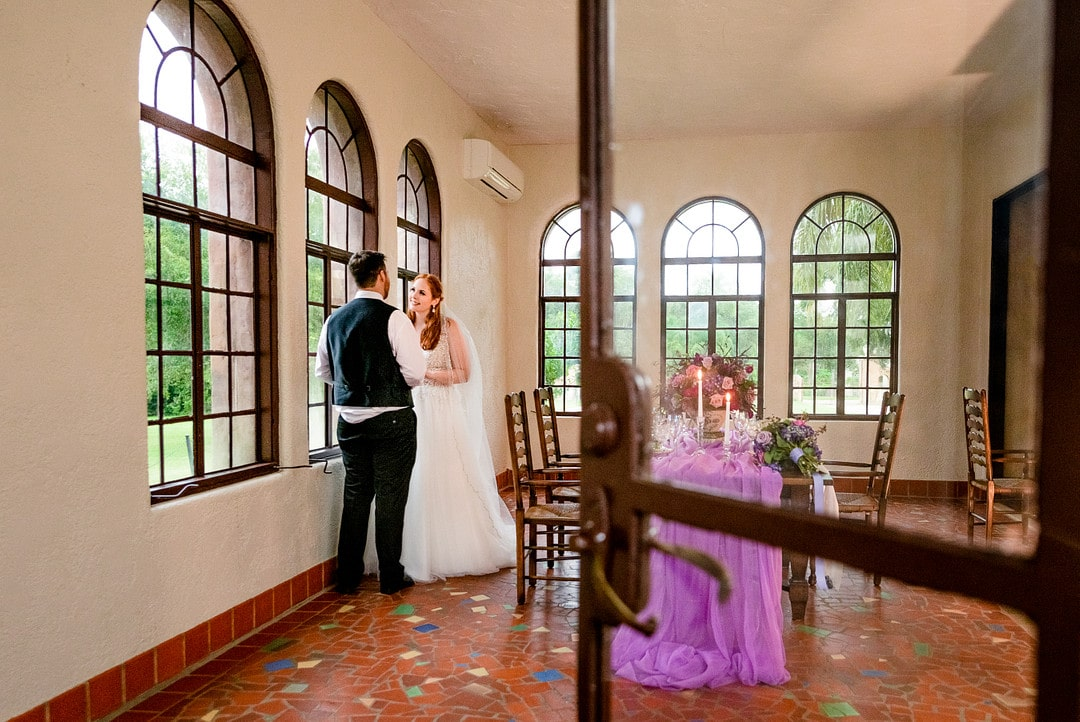 bride and groom in room next to decorated tabled for wedding day with door open in the shot