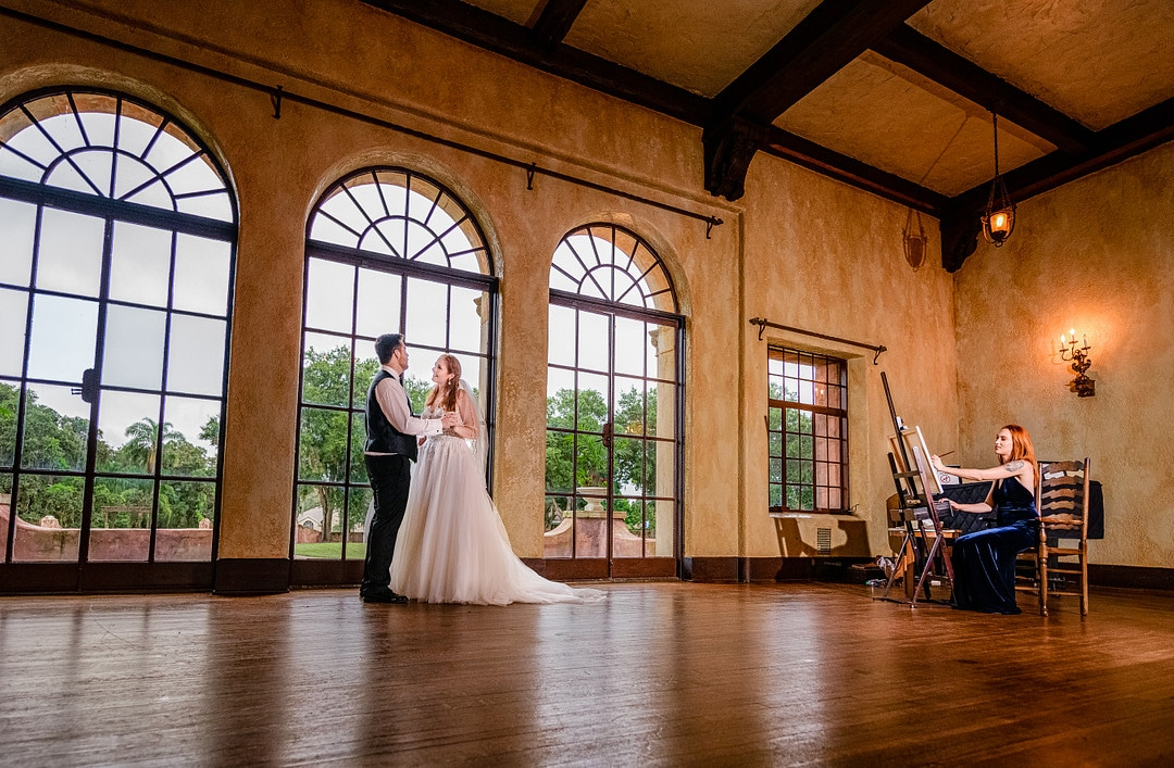 bride and groom dancing with each other in ballroom of historic wedding venue in front of floor to ceiling windows as live event painter works off to the right side of the image