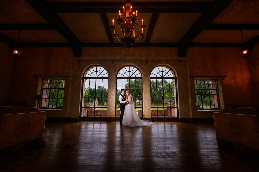 dark and moody shot of bride and groom under chandelier in ballroom of wedding venue in front of three windows