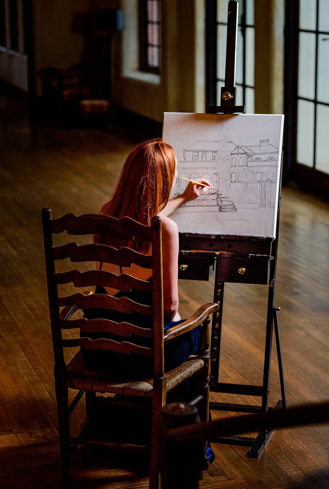shot from behind live event painter drawing the historic wedding venue on easel sitting down in wooden chair