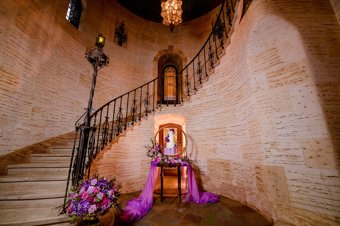 staircase at wedding venue with wrought iron railing and giant floral arrangement at bottom of staircase with cake table decorate with golden hoop cake stand and three tiered wedding cake