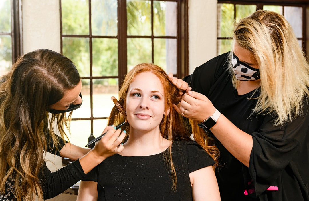 red headed bride in black shirt getting hair and makeup done professionally on wedding day