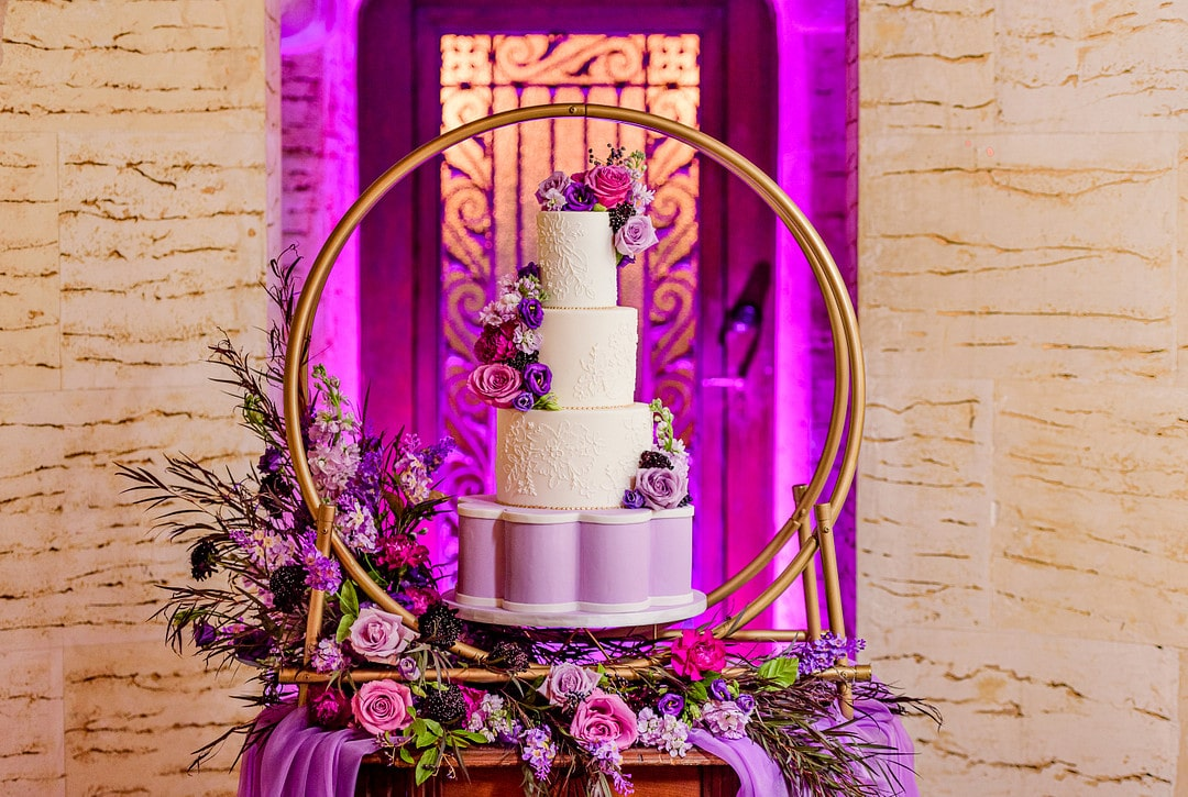 wedding cake sitting on golden hoop cake stand atop a floral decorated tabletop in front of archway at wedding venue with bright purple uplighting behind it