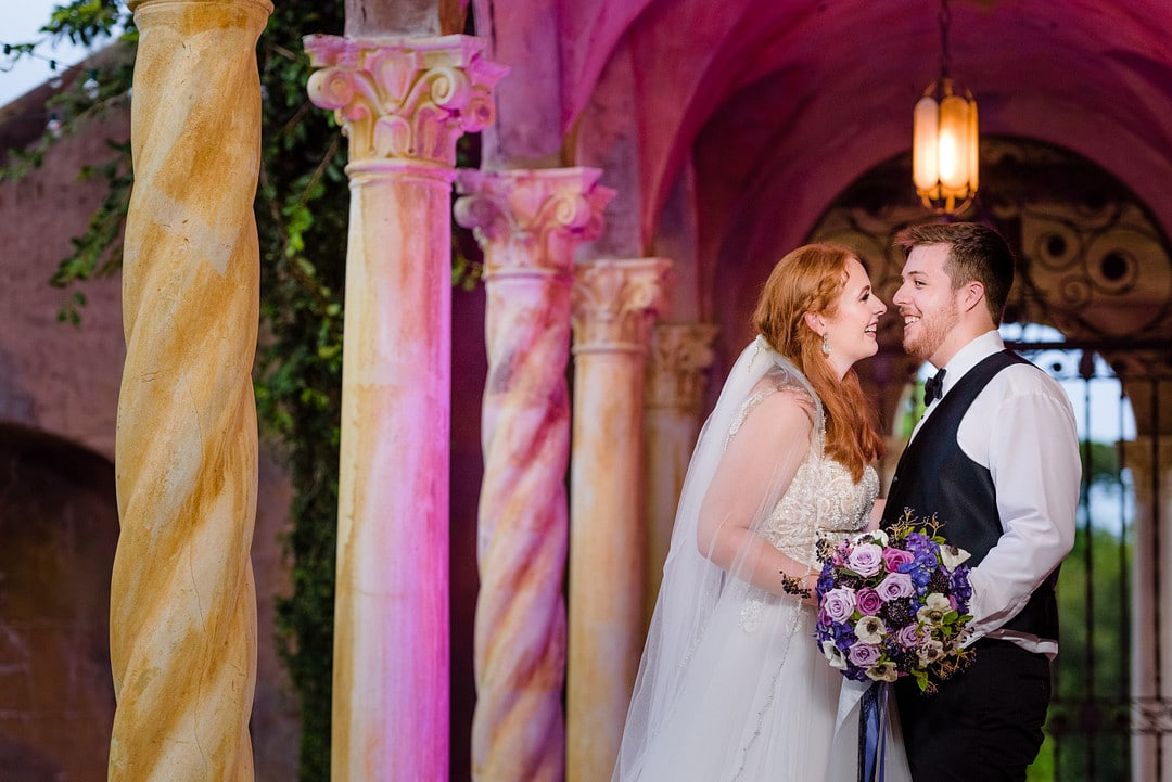 bride holding vivid purple bouquet and groom smiling at each other lovingly on their florida fairy tale castle wedding day outside their wedding venue next to special columns