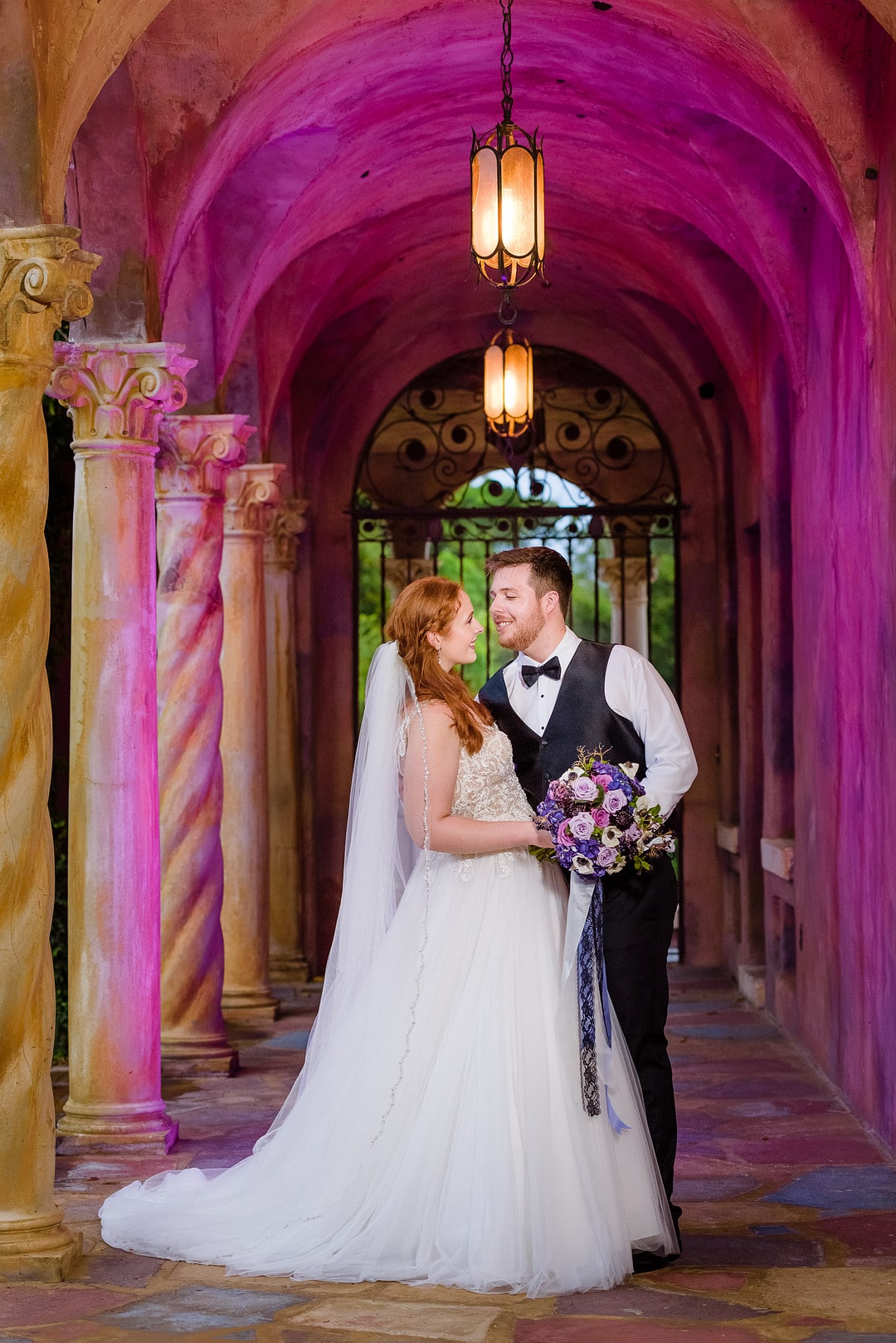 bride holding bouquet with groom missing tuxedo jacket taking wedding portrait in archway of the outdoor porch of wedding venue with bright purple uplighting
