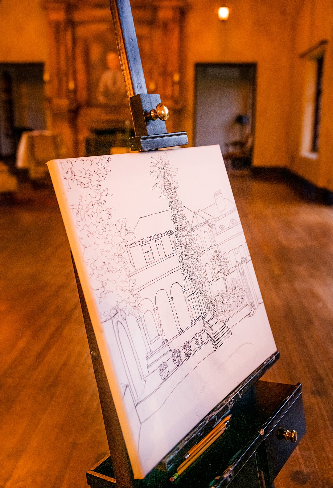 final painting from live event painter at wedding depicting the line drawing of the historic wedding venue on easel with fireplace in the background