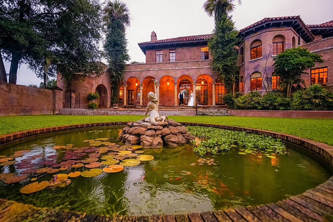 outdoor courtyard of historic florida wedding venue the howey mansion with pond and lily pads with historic statue in the middle and bride and groom off in the distance on the venue back porch