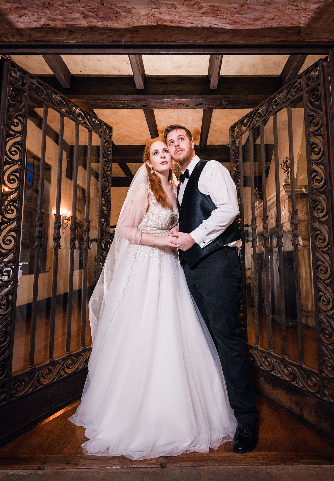 bride and groom holding each other looking off into the distance near wrought iron doors of wedding venue