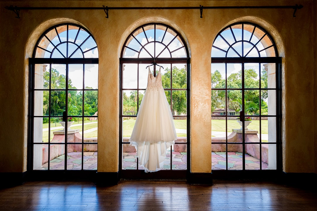 wedding dress hanging in the middle window of three floor to ceiling windows with arch window at the top of each looking from inside to the outdoors