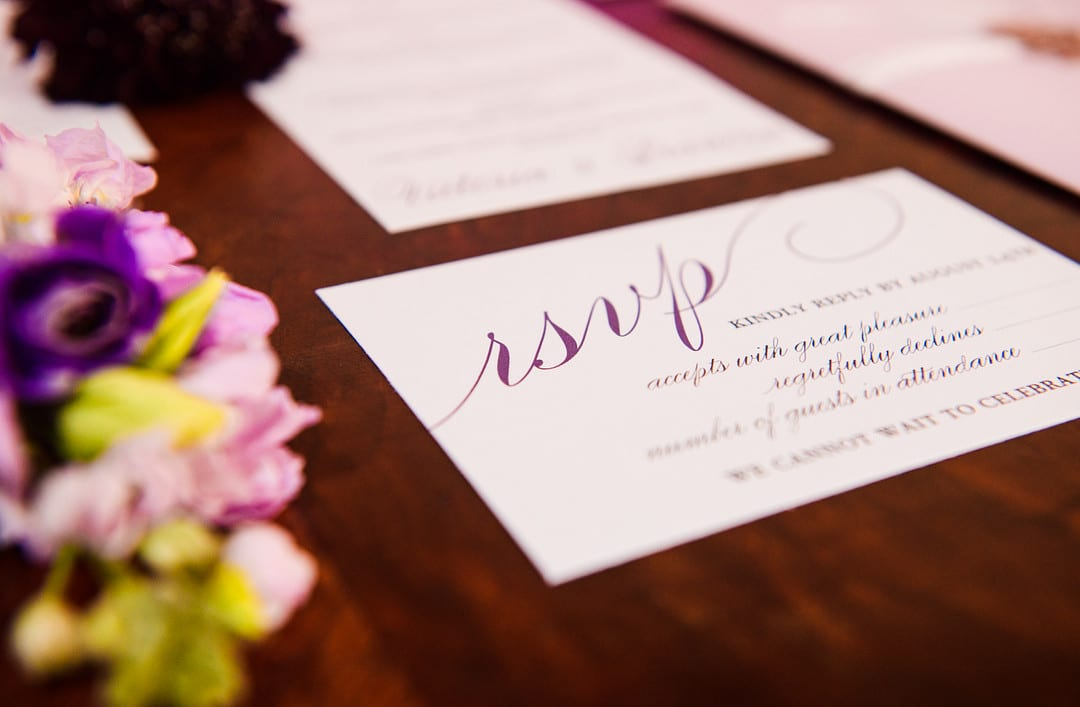 close up shot of rsvp card for wedding invitation on table with other calligraphy pieces