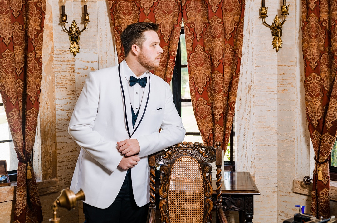 groom in classic white tuxedo with black bowtie leaning against antique chair in front of patterned curtains