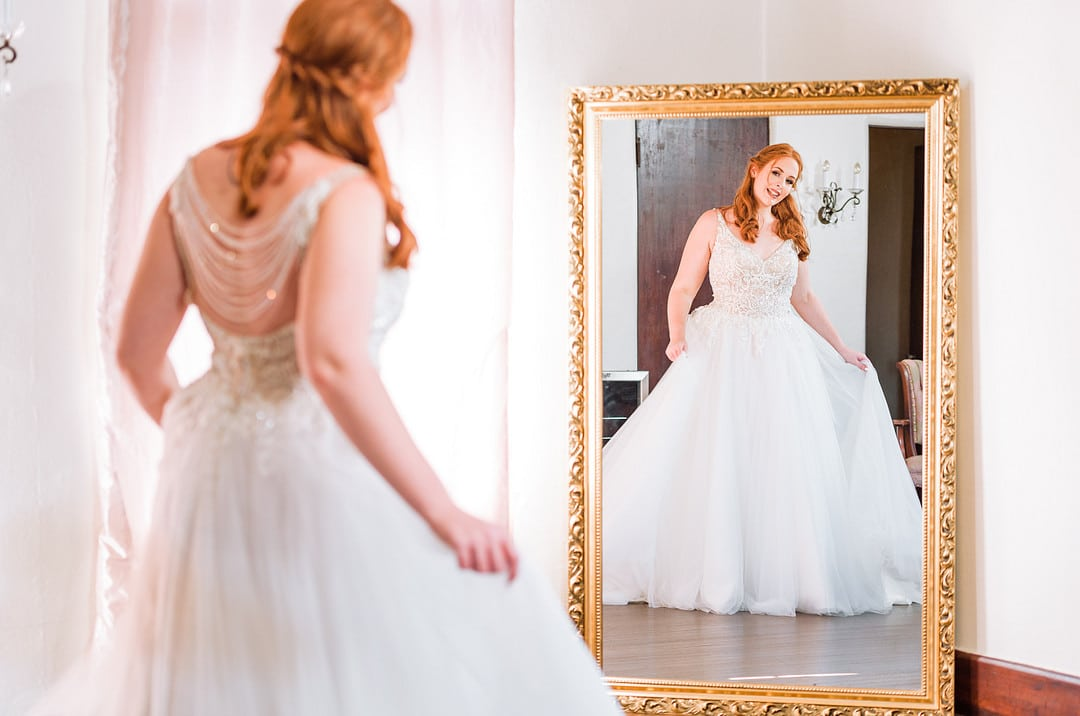 red headed bride in ball gown wedding dress looking into a full length mirror