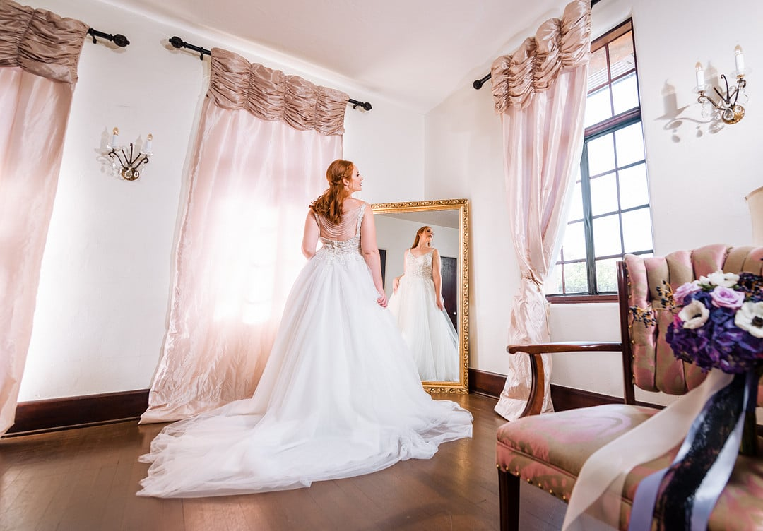 wide room shot of bride in wedding gown standing in front of floor length mirror with bouquet off to the side of the image