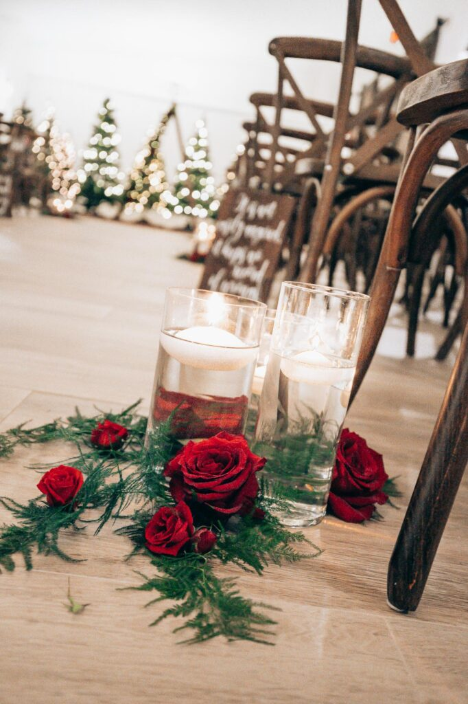 red roses and floating candles as decorations for inside wedding ceremony at The Grand Ol' Barn