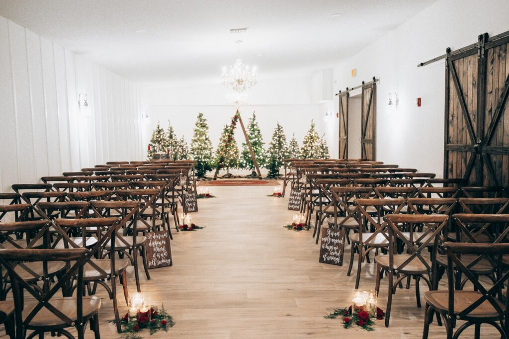 room setup for inside wedding ceremony at The Grand Ol' Barn, with wooden barn doors on the right and wooden chairs with Christmas trees, red roses, and floating candles