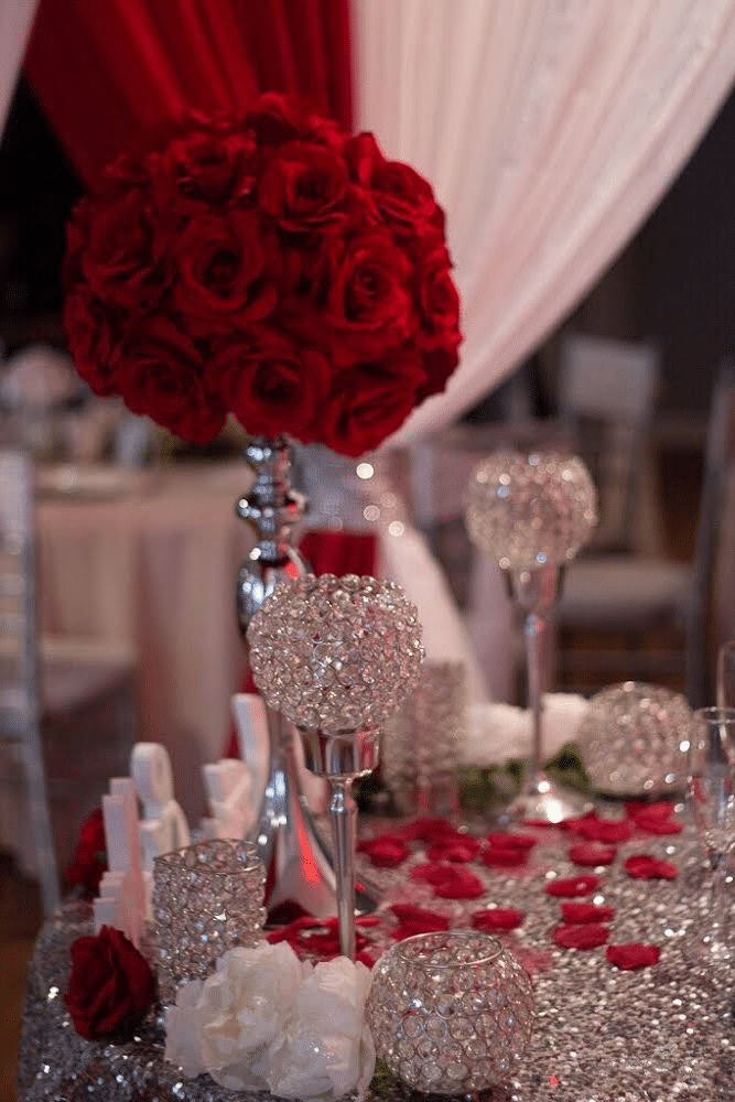 sparkly candle holders with tall red floral arrangement in center and red rose petals on table