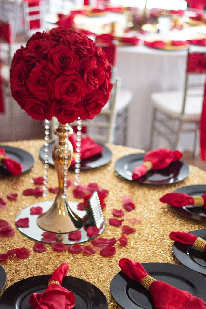 ball of red roses in gold vase on top of gold table with black and red details
