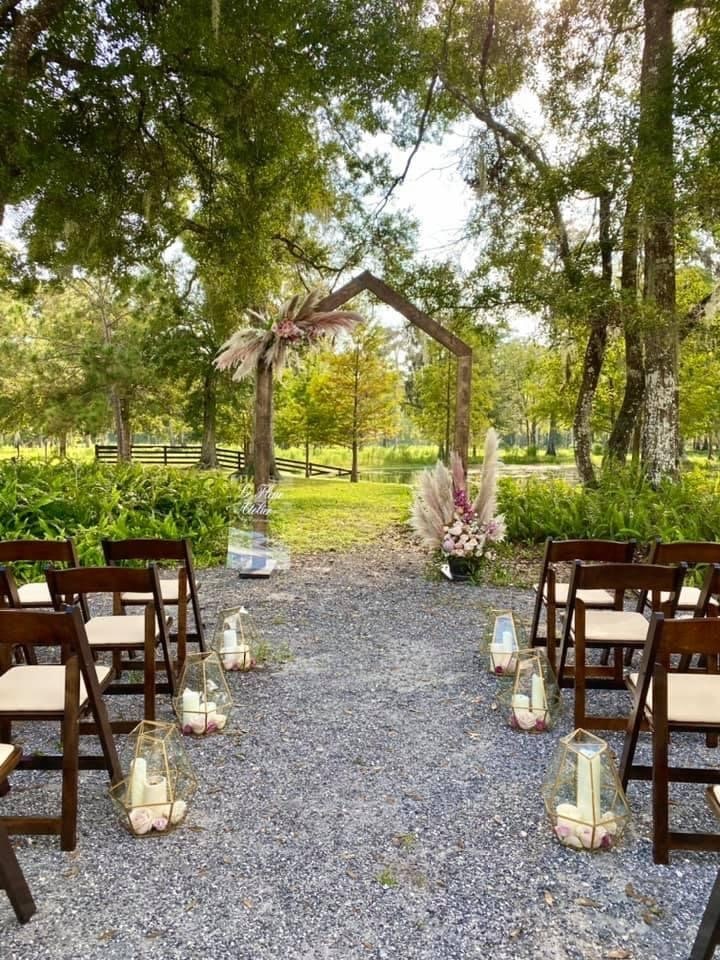 outdoor wedding ceremony at Cypress Creek Farmhouse with wooden arch setup in the shade of large trees and dark chairs set up, with candles lining the aisle